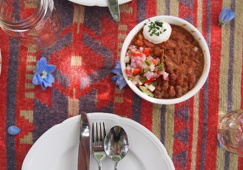 tired of the usual rental wedding linens? try Turkish rugs to spice up your table decor.