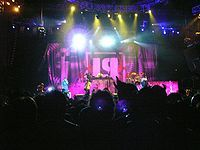 Nu Metal-- (also known as nü-metal and aggro-metal) is a form of alternative metal that combines elements of heavy metal music with elements of other music genres such as hip hop, alternative rock, funk and grunge. Nu metal bands have drawn elements and influences from a variety of musical styles, including multiple genres of heavy metal. Nu metal rarely features guitar solos; the genre is heavily syncopated and based on guitar riffs. Many nu metal guitarists use seven-string guitars that…