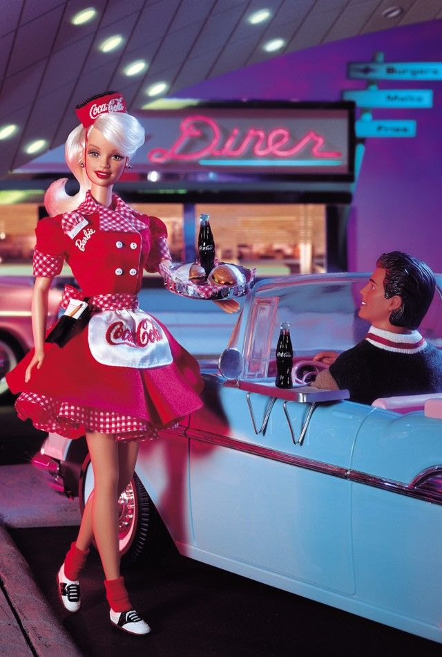 "Coca-Cola® Barbie® Waitress. You'll surely want fries with your COKE®, when she greets you in her COKE® red + white uniform with matching gingham print trim. Capturing a slice of American pie, she looks as nostalgic as the COCA-COLA® trademarks adorning her apron, waitress cap + ""bottle-top"" serving tray. Her uniform sports a Barbie® monogram + gingham print hankie. Reminiscent of the times, Barbie® wears black + white saddle shoes, a playful ponytail, with her ""writing tablet"" ready."