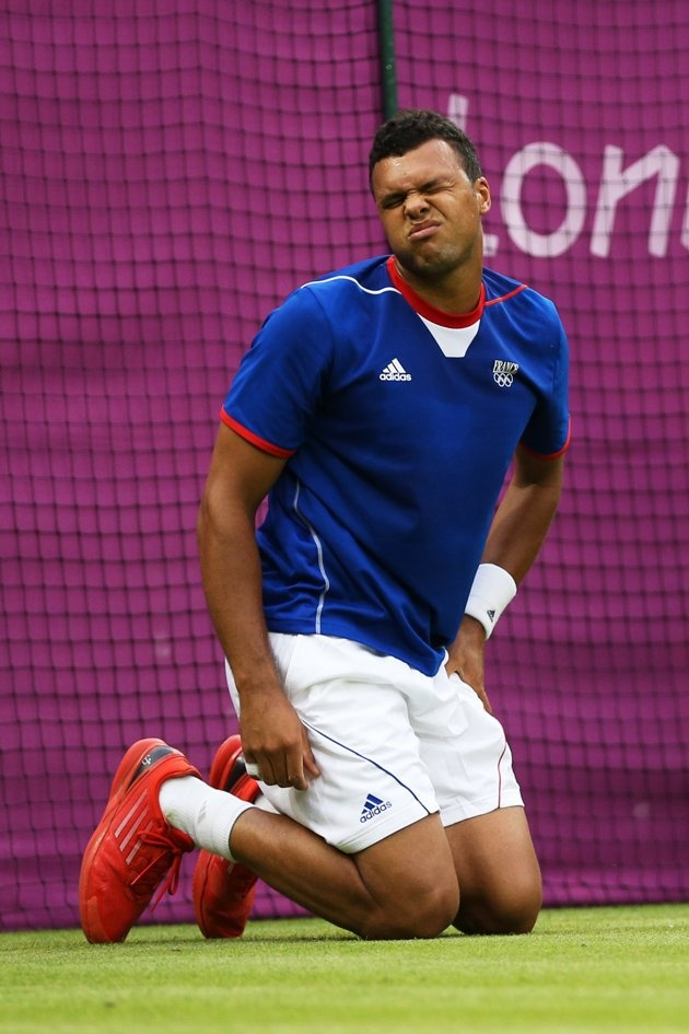 Jo-Wilfried Tsonga of France grimaces after taking a fall during the Men's Singles Tennis match against Thomaz Bellucci of Brazil on Day 2 of the London 2012 Olympic Games at the All England Lawn Tennis and Croquet Club in Wimbledon on July 29, 2012 in London