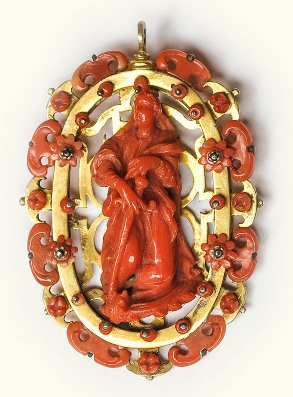 Red Coral and Gilt Copper Pendant. Trapani (Sicily), 17th century. 5,5 x 8 cm. Standing out in the centre of this tasteful coral and gilt copper pendant is the figure of Saint Catherine of Alexandria, who can be recognised through her customary attributes: the sword and the wheel. -Cesati Works of Art-