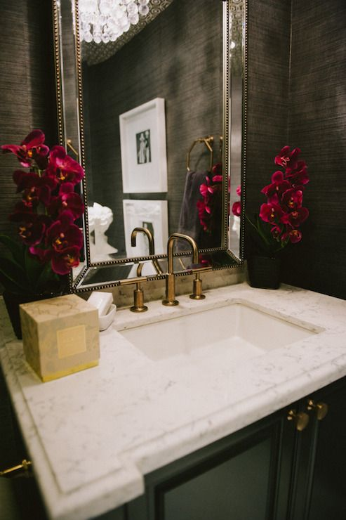 Meredith Heron's Office - Beautiful powder room with dark gray grasscloth wallpaper framing beveled beaded mirror over black vanity topped with white marble beveled countertop: