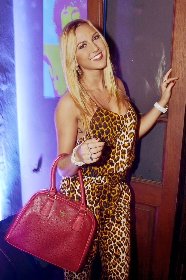 cheetah jumpsuit and red leather bag.