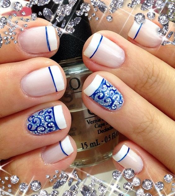 Beautiful white and blue French tips. Use the white polish as your French tip and paint on pretty and detailed lace designs in blue hues and white polish on your nails.: