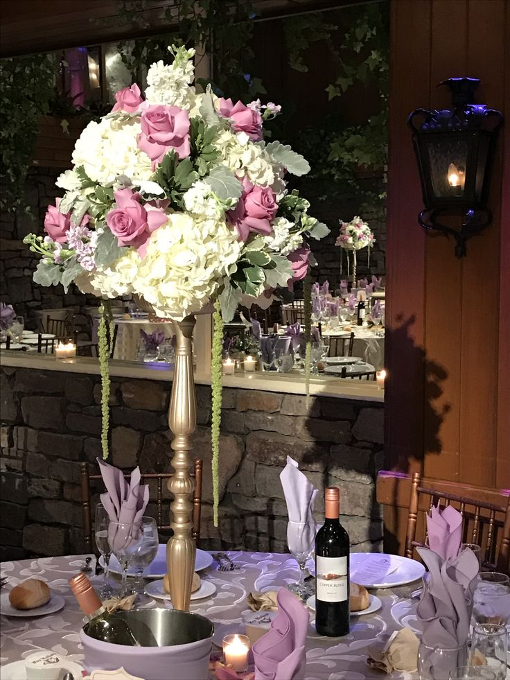 Tall wedding centerpiece on a gold pedestal with an arrangement of white hydrangea, cool water roses, apple blossom stock, dusty miller, variegated pit and green hanging amaranthus. Fox Hollow.