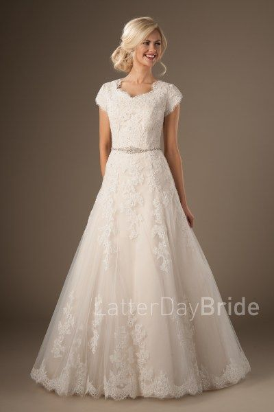 Hartwell |  We love the soft eyelash lace on the neckline and sleeves and the scallop at the bottom of the train. If you've been looking for the perfect ballgown, you just found it!    Style Love: The buttons go all the way down the train! Pair this gown with a veil edged in silver sparkle to tie the look together!    Gown available in Ivory/Deco Gold (as pictured), White/White, Ivory/Ivory, or White/Deco Gold    Find at LatterDayBride.com and in Store in SLC, UT