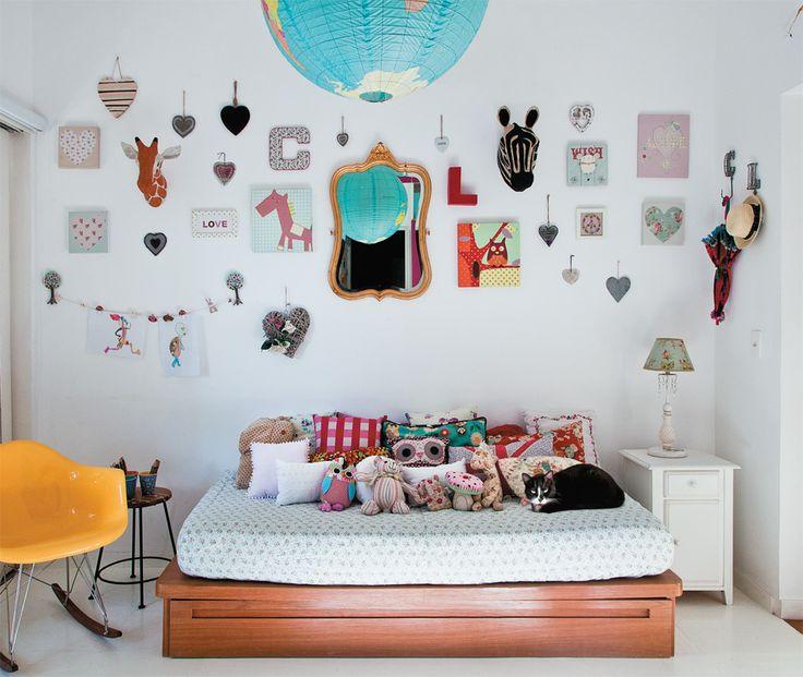 Neste quarto, a composição de quadros na parede revela as referências culturais do morador. Coloridos e com diferentes tamanhos, a composição na parede também admite outros acessórios e deixa a parede da cabeceira ainda mais descolada.