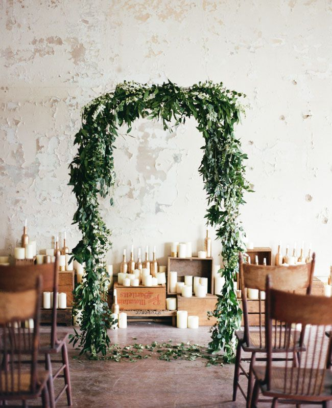 green garland ceremony arbor with candles in the background for a rustic, industrial feel
