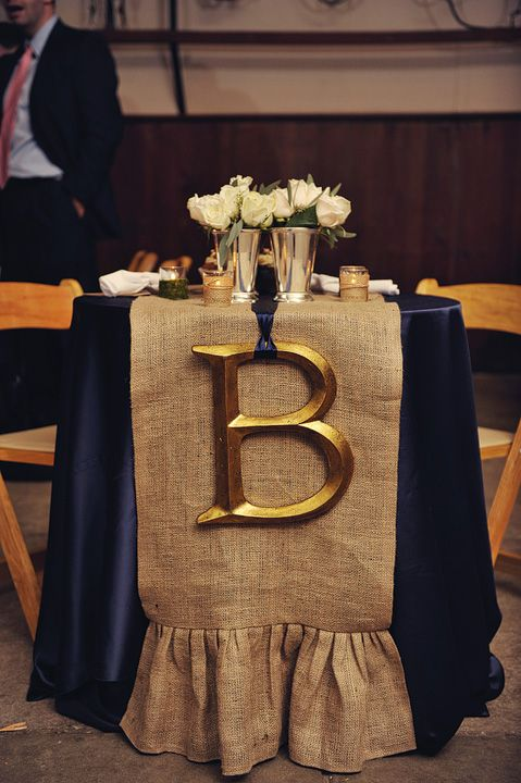 Love the table decoration (especially the gold initial) but I wouldn't use burlap behind it, maybe something different