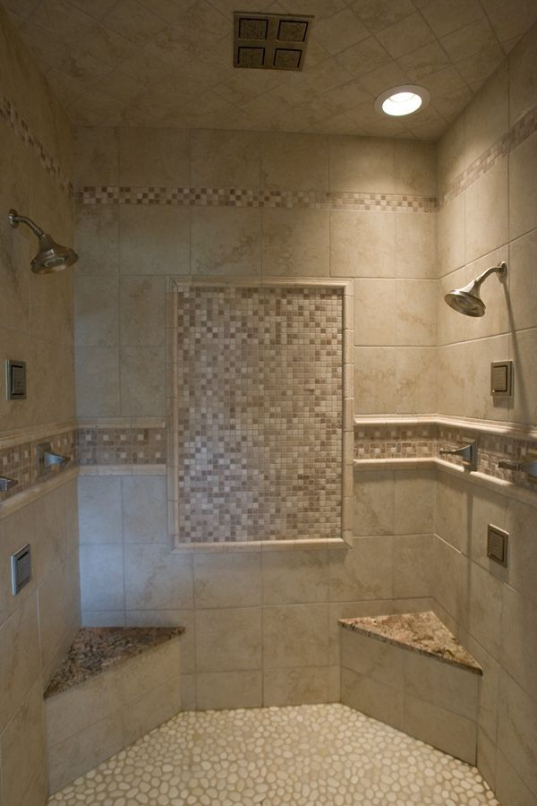 Walk-in tile shower with tile accents, a pebble floor, two corner seats with granite on top, a rain head, and two shower heads.