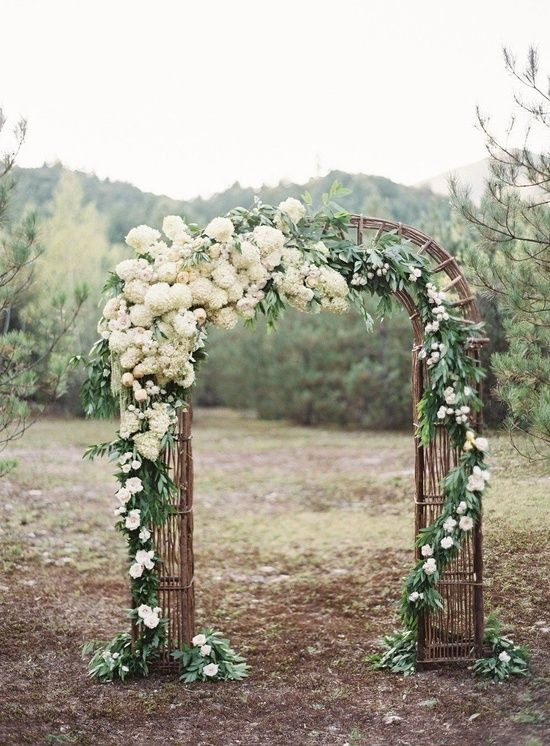 floral installation on wooden arch.