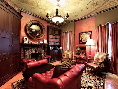 This traditional home library design is filled with rich wood and leather furniture. The red Venetian plaster on the walls complement the located in front of the fireplace dark red chaise and the custom ceiling antique map.     Design: Jennifer Duneier