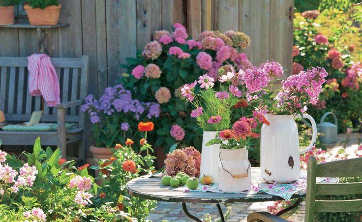 Wasserkrug und Milchkanne aus Emaille findet man manchmal noch in Großmutters Küchenschrank. Jetzt kommen sie als Vase für Phlox, Zinnien und Schmuckkörbchen zu neuen Ehren. Dass Gefäße und Tisch Gebrauchsspuren haben, macht ihren Charme erst aus
