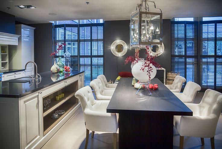 Nowoczesna, otwarta kuchnia z wyspą kuchenną i jadalnią. Szafki kuchenne białe z czarnym blatem. Stół drewniany czarny z zestawem białych krzeseł. Piękne, szklane lampy na ścianie oraz nad stołem ||  Modern, open kitchen with kitchen island and dining area. Kitchen cabinets are white with black top. Black wooden table with a set of white chairs. Beautiful glass lamps on the wall and above the table