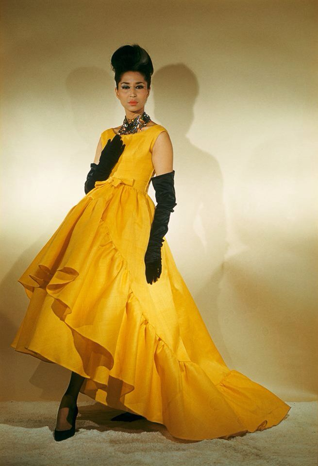 Balenciaga 1959. China Machado model magazine designer couture vintage fashion style late 50s early 60s evening gown short front longer in back ruffle hem gloves shoes necklace updo hair yellow gold black accent accessories