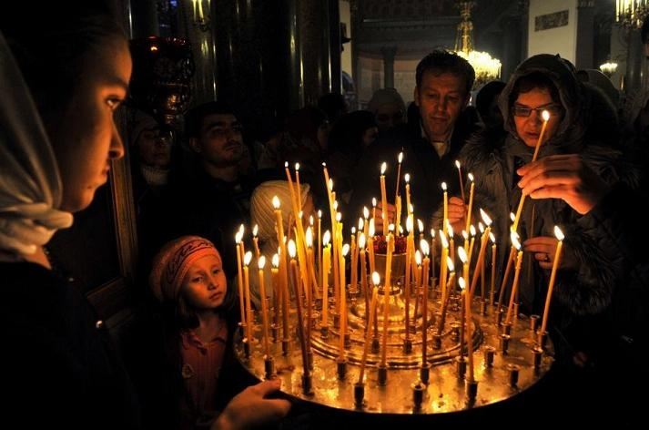 Lighting candles inside a Russian Orthodox church.