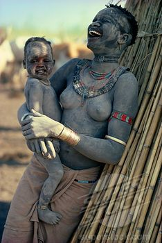 Sudan, Mundari, 'Agar Dinka Woman Decorated With Dust, Holding Young Son In Her Arms And Laughing. Woman Wearing Marriage Beads Around Her Neck And White Ivory Bracelet On Her Arm.' | Stock Photo 1850-7267 : Superstock