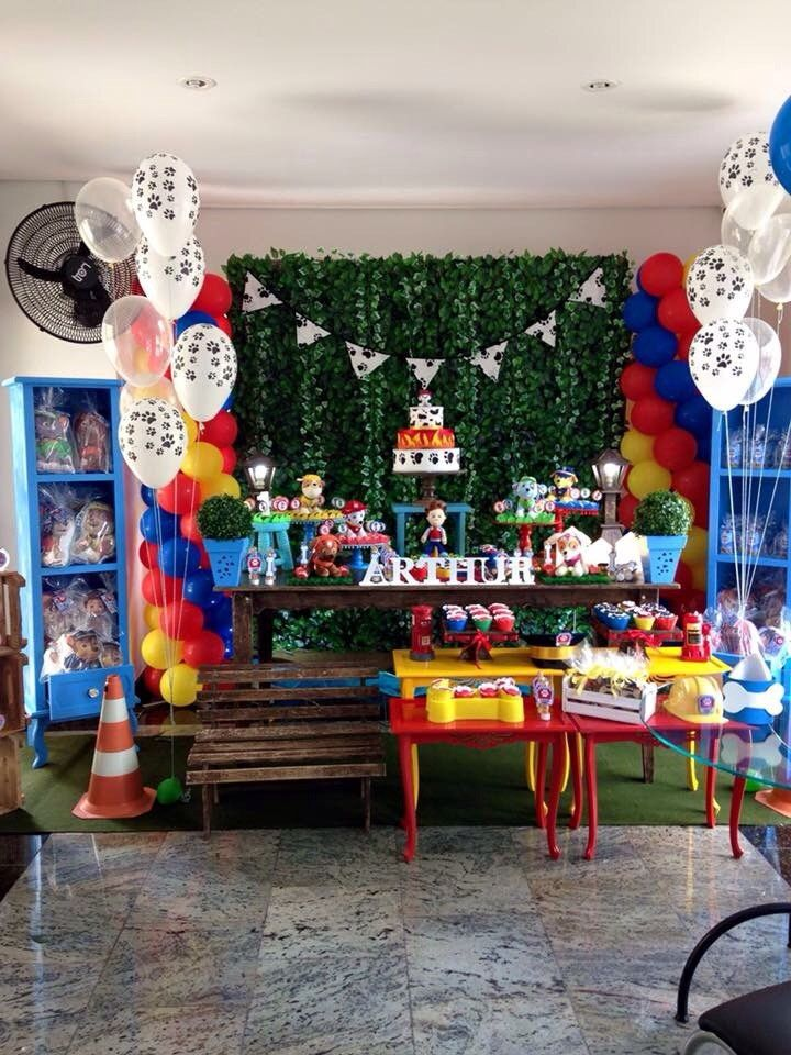 Mesa decorada para festa infantil  Patrulha canina  Personagens originais  Fundo com muro inglês  2 torres de balões  2 estantes azuis  2 mesas baixas amarelas  2 mesas baixas vermelhas  Caixotes  Bandejas  Bolo cenográfico