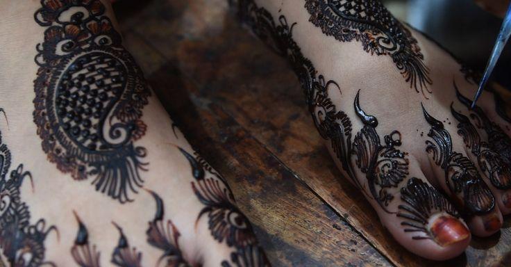 Mulher faz desenhos com henna no pé de uma garota que se prepara para as festividades do Eid al-Fitr, feriado que marca o fim do Ramadã, em salão de beleza de Karachi, no Paquistão