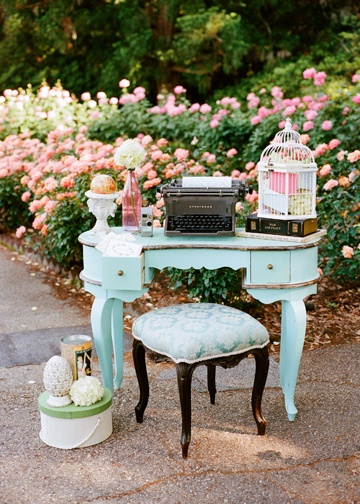 A turquoise vanity serves as a registration table with an old typewriter as a guestbook. #vintage #wedding