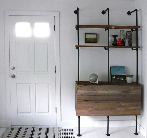 This custom made shelving unit's design could be adapted to attach to the ceiling or header instead of returning backwards to the wall and a back panel can be added, turning the piece into a space divider.