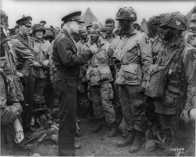 Dwight Eisenhower meets with 1st Lieutenant Wallace C. Strobel and men of Company E, 502nd Parachute Infantry Regiment prior to their night jump into Normandy (Image)