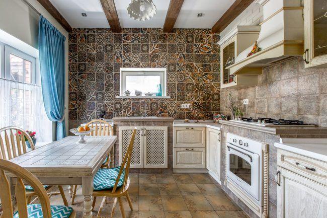Ярко-голубые шторы в цвет седушек на стульях и мозаичный кафель с рисунком на стене в кухне стиля кантри
