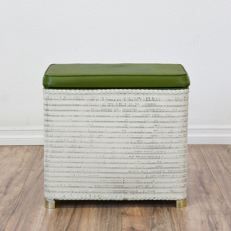 This tropical bench is featured in a woven wicker rattan painted in a fresh white. This storage stool is in great condition with a green upholstered seat cushion, brass feet and large interior hamper cubby. Unique ottoman perfect for storing! #tropical #storage #storageottoman #sandiegovintage #vintagefurniture