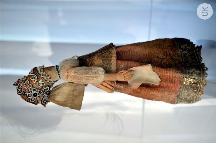 XVIII - XIX век. 25 см, одета она в праздничный костюм Севера – сарафан и душегрею из шёлковой набивной ткани, украшенные металлической тесьмой. На голове – девичья повязка и поверх неё – прорезной «венец», украшенный блёстками, мелким «монастырским» бисером и металлическим галуном. Изображение лица символично и уходит своими корнями в традиции древнерусского художественного шитья. Вышитые глаза в форме косточек, соболиные брови, сжатые губы рубинового цвета и
