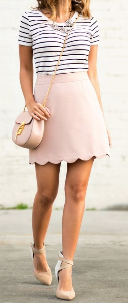 Stylish woman is wearing a pink scallop mini skirt and a striped T-shirt. This outfit combines two girly favorites into a cute, warm weather ensemble.