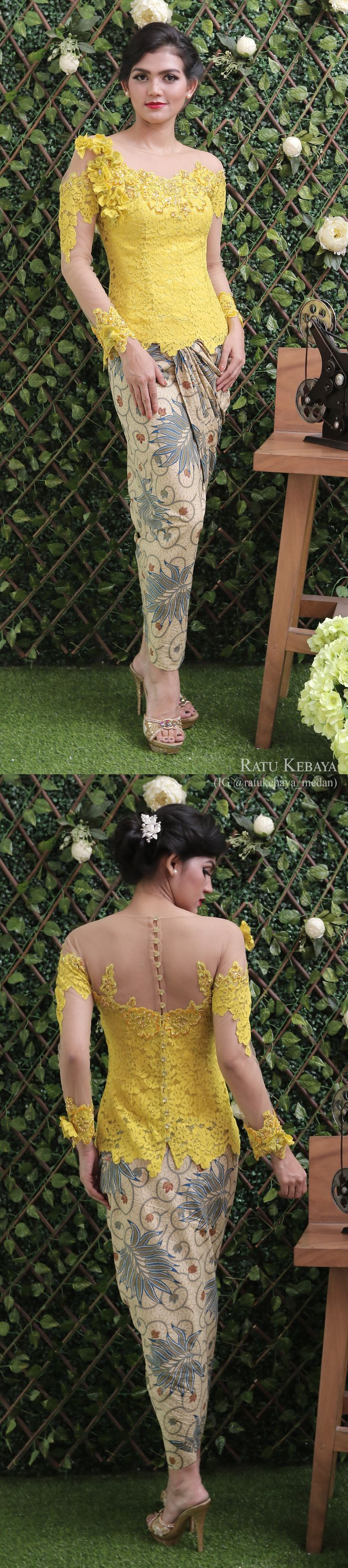 Kebaya kuning dengan aplikasi bunga bahu, dikombinasi dengan rok lilit batik (IG @ratukebaya_medan)