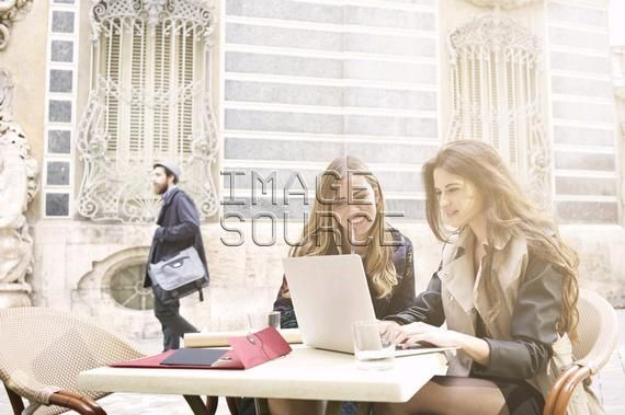Two young women looking at laptop outside Museum of Ceramics, Valencia, Spain