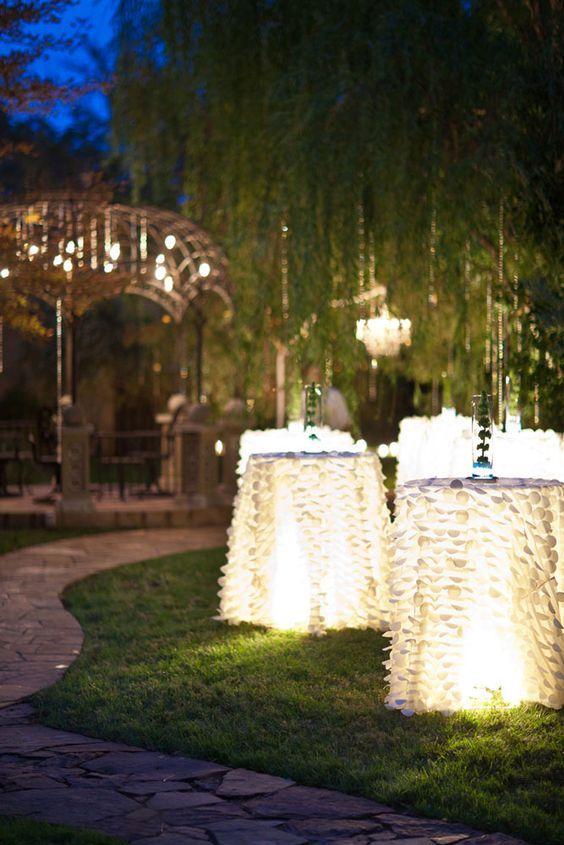 Cocktail Tables, Petal Taffeta Linens, and Lights #forestwedding #foresttheme #enchantedforest #outdoorweddingreception #weddinglighting #lightuptables #lituptables #leafpetallinens #tablerentals #lighting