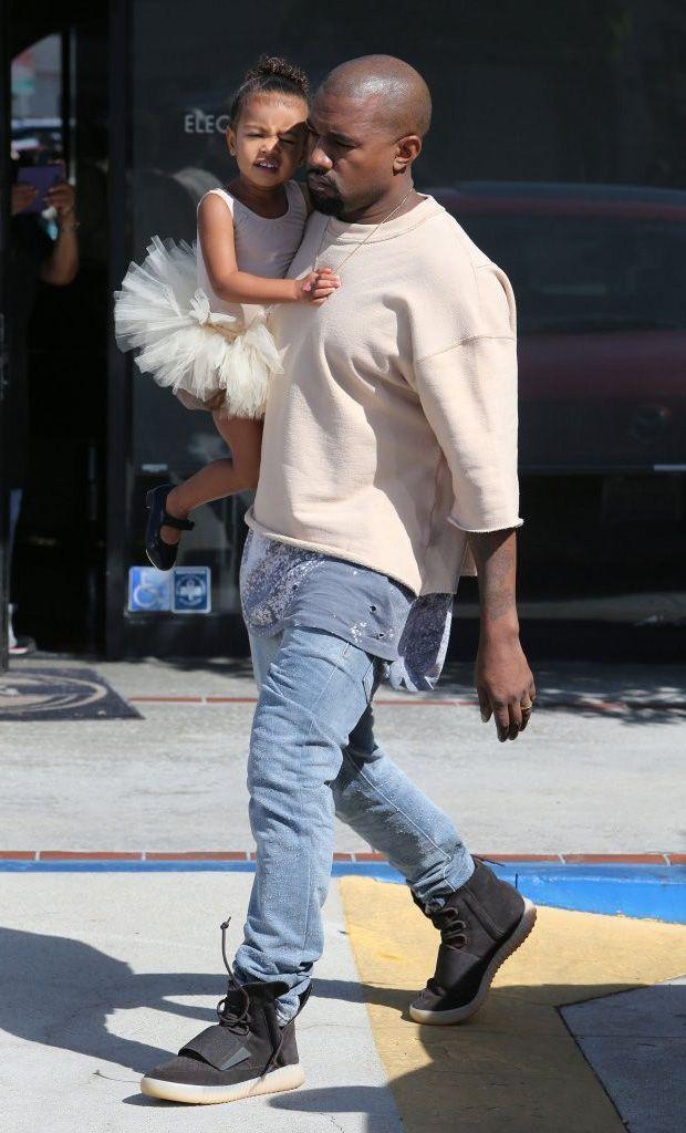 Kanye West wears Fear of God Sweatshirt and Black Yeezy 750 Boost Sneakers  in Los Angeles