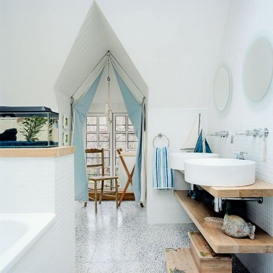 Driftwood-style worktops are combined with pebble vinyl flooring for a quirky beach feel in this bathroom. Twin basins save arguments in the mornings, and the curtains resemble sails of a boat.