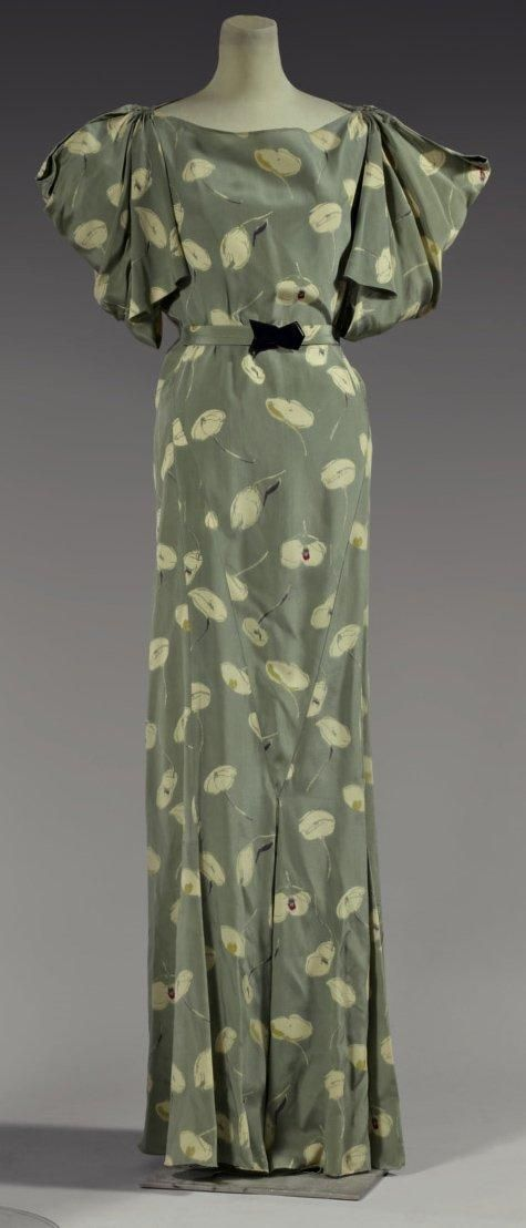 Wedding Garden Party by Madeleine Vionnet, 1934, model No. 4750. Printed silk crepe, sowing abstract flowers ivory sage green background. Short sleeve cutouts giving a draped skirt at the bottom extended pleats. Fabric belt with black bakelite clasp.