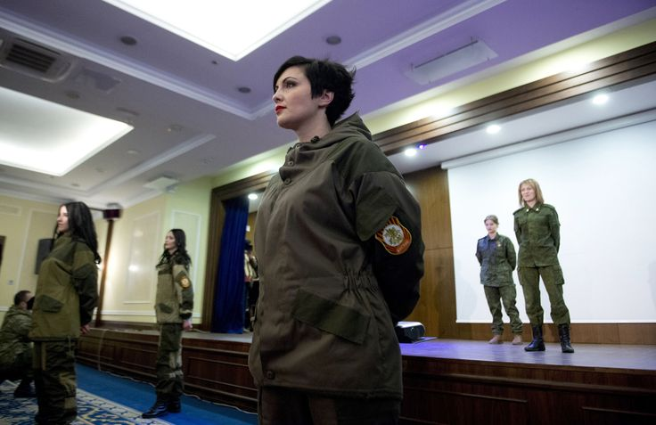 Women operating in a combat battalion of the self-proclaimed People Republic of Donetsk (DNR) stand to attention after taking part in a fashion show in Donetsk on March 7, 2015.
