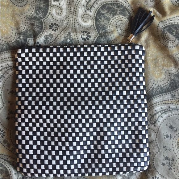 Black and white clutch Black and white checkered fold over clutch with fringe zipper pull. Inside is in good condition and had black and white stripes. No trades. Bags Clutches & Wristlets