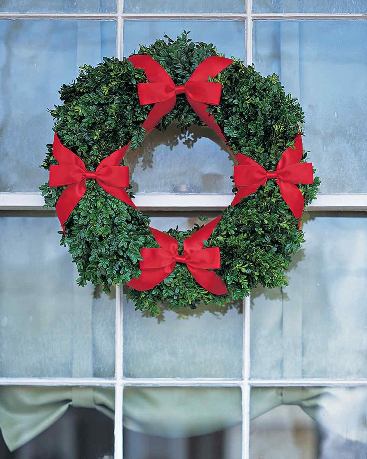 Four-Bow Boxwood Window Wreath Holiday Decor Ideas | Martha Stewart Living — The shiny green foliage of a boxwood wreath embellished with a quartet of slim satin bows captures the classic Christmas pairing of red and green.