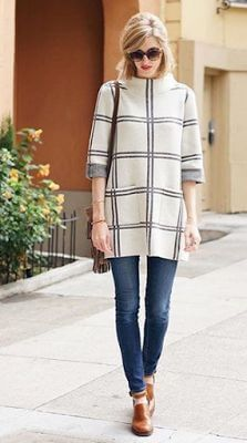 A woman is wearing a tunic sweater with blue jeans