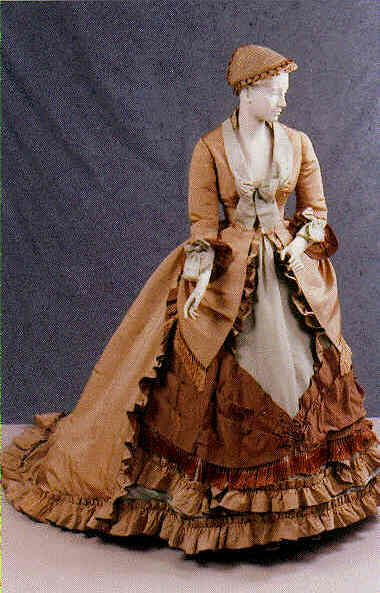 1869-1870 Day coat/suit by Worth - Two piece walking suit consisting of a skirt and jacket of beige silk faille trimmed with brown and light blue faille and silk fringe.