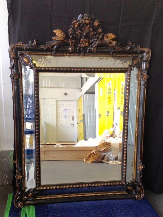 Grote Napoleon III overmantel kussen spiegel met de hand gesneden ebonised en verguld hout en gesso frame - eind 19e eeuw  Een overmantel spiegel van Napoleon III met ebonised onderstel (zwart). Hand gesneden met een versierde kuif (bloemen en vogels). Alle van de hand gesneden details worden gemarkeerd in een vergulden brons/goud. De spiegel heeft een groot centraal gedeelte en vier panelen alle met originele schuine rand geslepen spiegelglas. Het originele glas is leeftijd/foxed in…