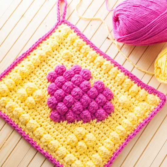 Bobble stitches create beautiful texture in this brightly-colored crochet heart potholder -- a modern twist on grandma's favorite craft! thanks so xox
