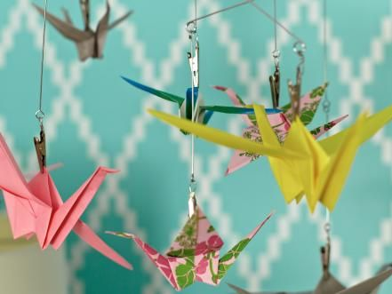 Origami birds, made with vintage wrapping paper in the colors from the inspiration piece, hang from an inexpensive photo mobile. This simple mobile adds a handmade touch and entertains the girls during nap time.  Best of the Blog: Create an Origami Mobile