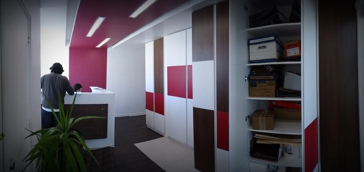 Hall de entrada con mesón de recepción. Panel cuadriculado para uso decorativo y utilitario, ya que es estante de guardado