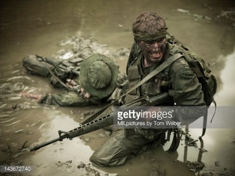 U.S. Special Operation Forces rifleman is pulling his comrade out of the mud.