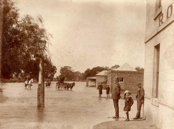 Glenorchy in flood, SLV.        The main street of Glenorchy under flood in Sept 1916. A policeman stands on the corner with a young girl behind him, and a man leaning against the wall of the Royal Hotel. In the middle of the street are two people on horses, and a three men in a horse-drawn dray. By O. Dolphin (his address in the 1916 directory is Royal Hotel, Glenorchy).