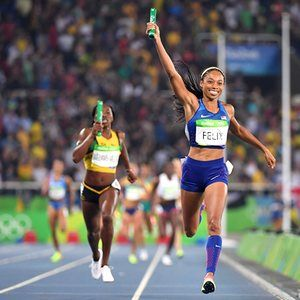 The USA's Allyson Felix holds her baton up as she crosses the finish line to win…