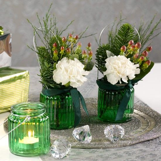 Use cute coloured-glass jars to create tealights for your festive table, reserving some to make mini foliage arrangements.