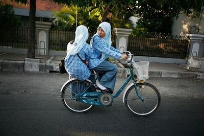 In East Java, a young Muslim Indonesian schoolgirl looks back at the traffic behind her as her friend sits sidesaddle on a bike they share on their way to school in Surabaya, Indonesia.  Photography by: